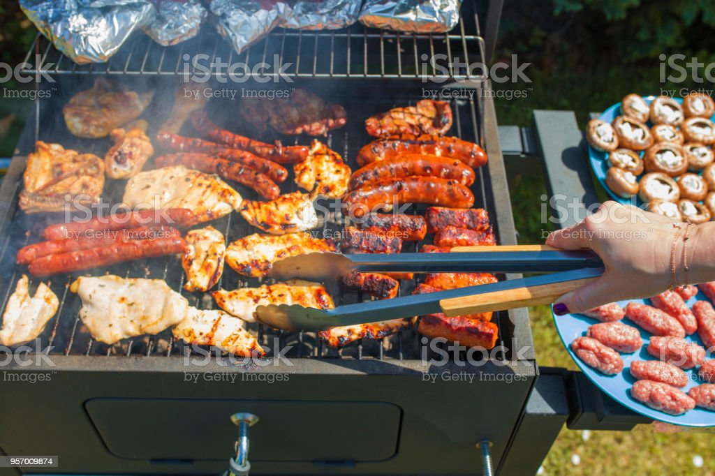 Grilling food on barbecue grill, hands preparing skewers stock photo