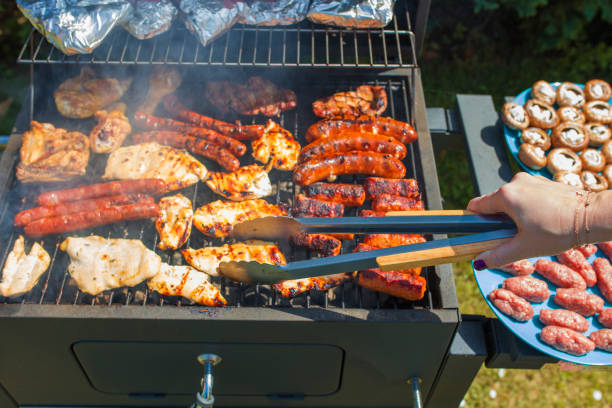 grilling food on barbecue grill, hands preparing skewers - barbecue grill stock photos and pictures