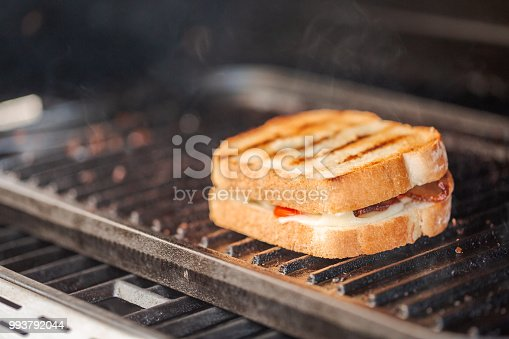 istock Grilling grilled cheese sandwich with bacon strips and fresh tomato on outdoor gas grill. 993792044
