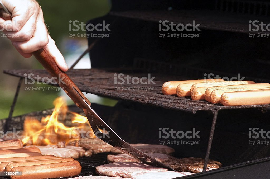 Grilling hamburgers and hotdogs at a summer party royalty-free stock photo