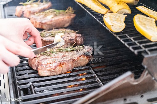 Grilling New York steak with a slice of butter and rosemary on an outdoor gas grill.