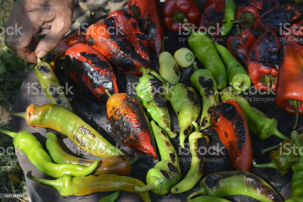 Grilling of green and red peppers on the old grill, for the preparation of delicious food in the Balkans named Ajvar stock photo