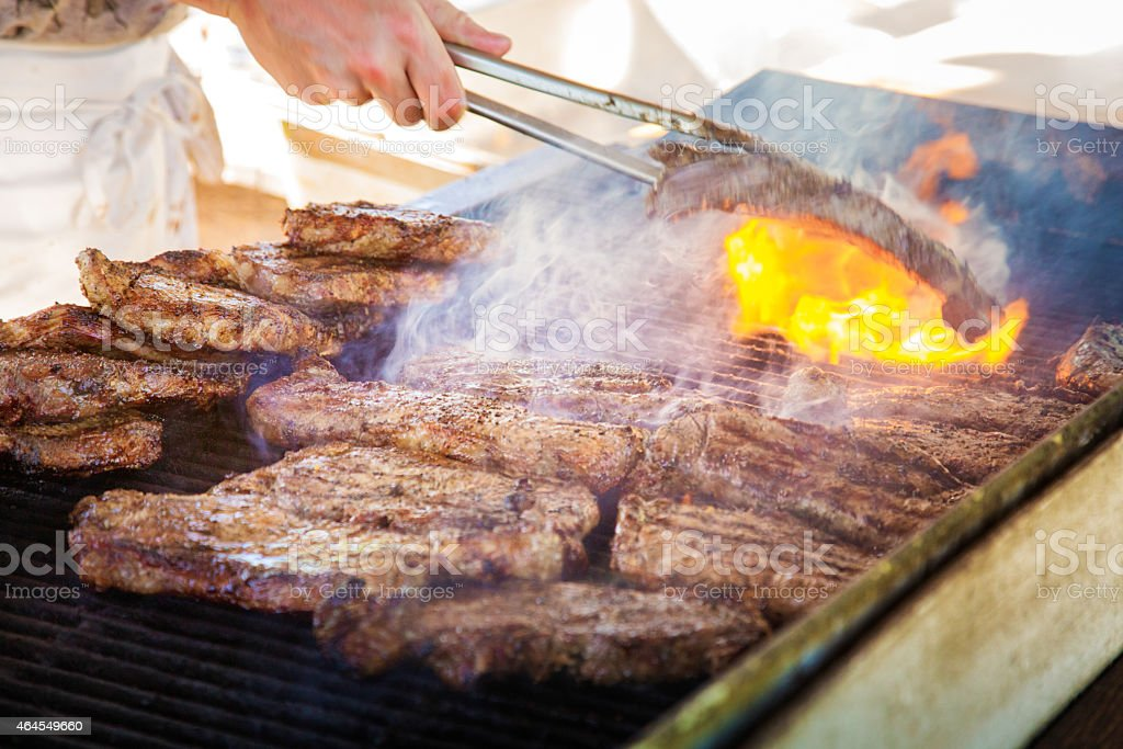 Grilling steaks on a flaming barbecue stock photo