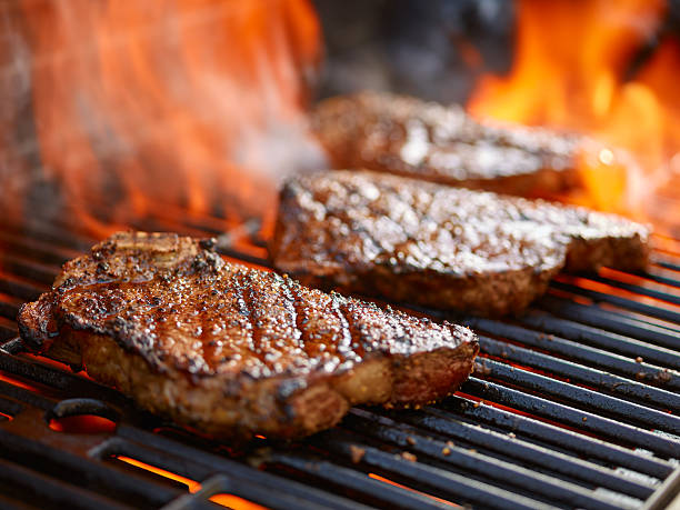 grilling steaks on flaming grill and shot with selective focus - barbecue grill stock photos and pictures