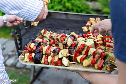 Grilling  delicious vegetables on skewers at an outdoor barbecue party