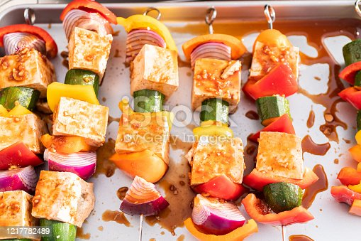 Grilling vegetarian tofu kebab with vegetables marinated in spicy sauce.