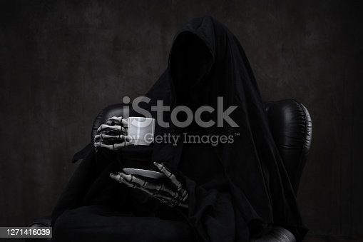 istock Grim Reaper drinking coffee, sitting in a classic leather chair. 1271416039