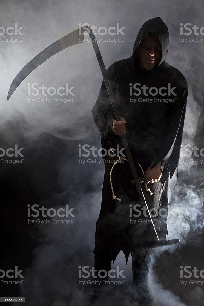 Grim reaper holding a scythe royalty-free stock photo