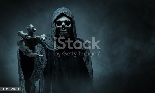 Grim reaper reaching towards the camera over dark misty background with copy space