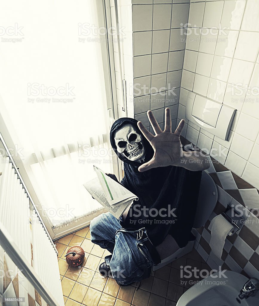 Grim Reaper sitting on the toilet royalty-free stock photo