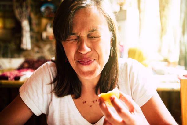 Grimace Woman eat lemon and make a grimace sour taste stock pictures, royalty-free photos & images