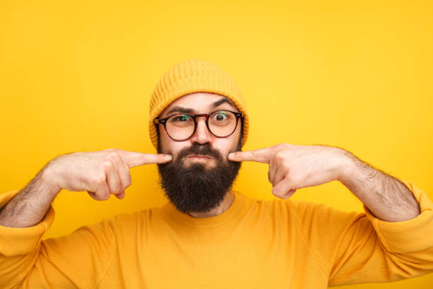Grimacing hipster making faces at camera stock photo