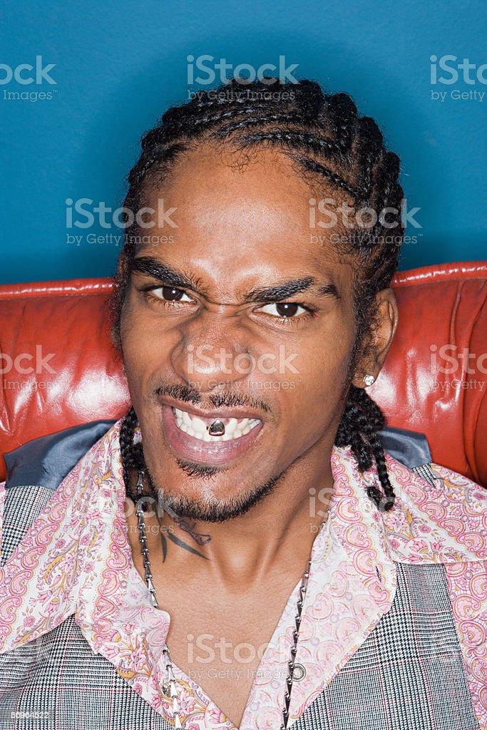 Grimacing man displaying gold tooth stock photo