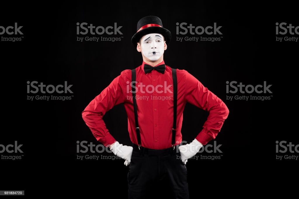 grimacing mime standing with hands akimbo isolated on black stock photo