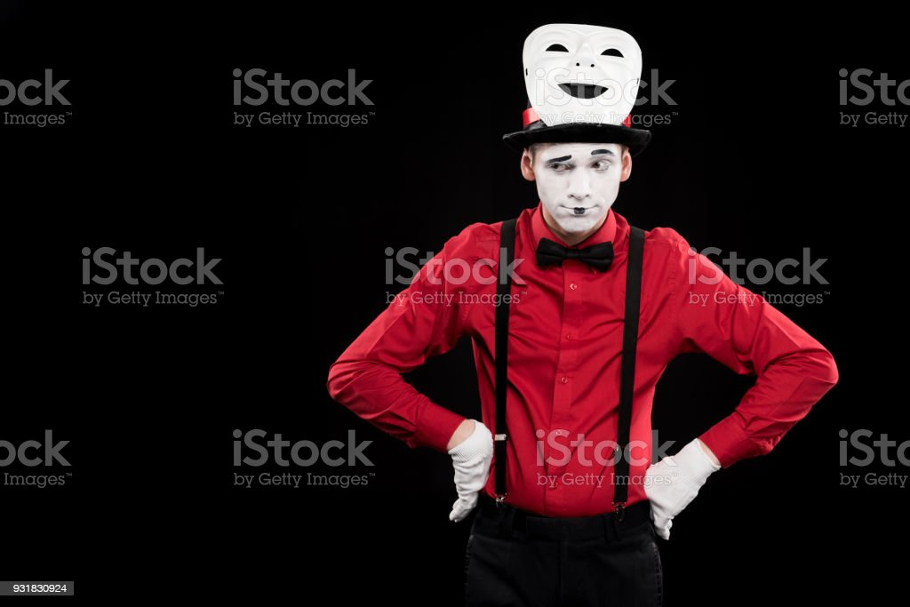 grimacing mime with hands akimbo and mask on hat isolated on black stock photo