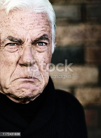 An old man grimaces, fed up and frustrated.