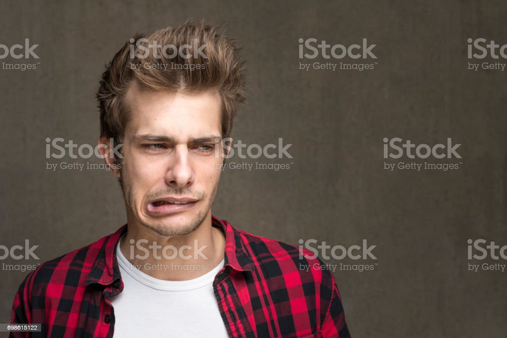 grimacing young man portrait stock photo