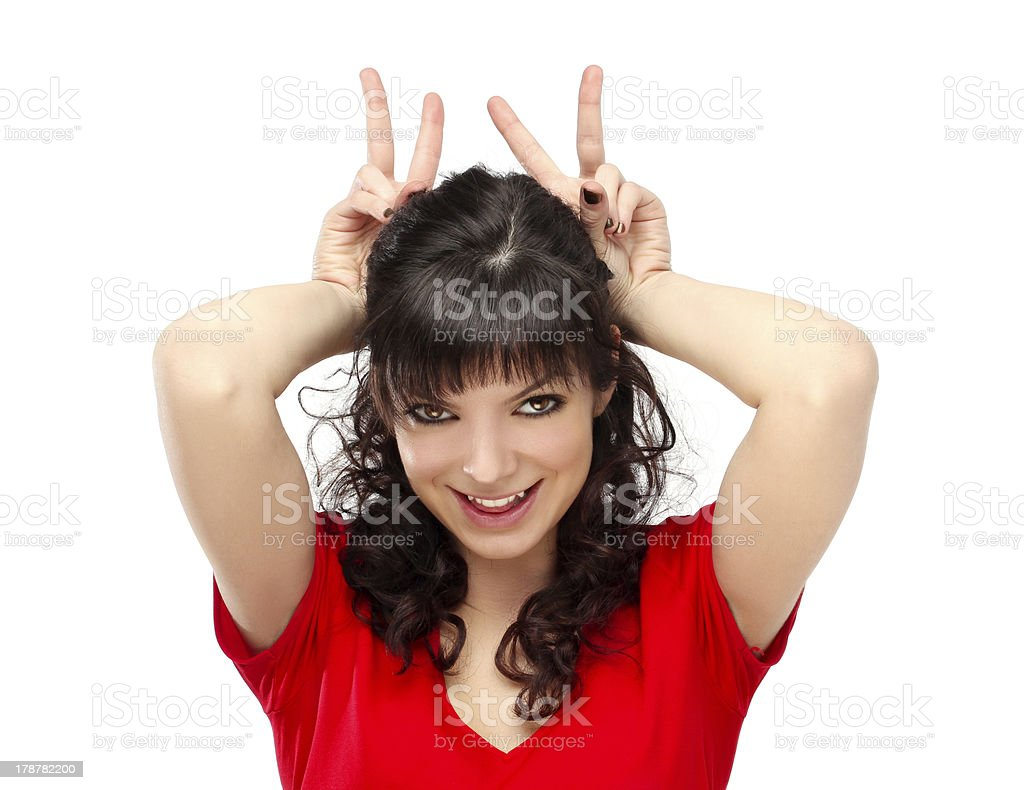 Grimacing.Funny woman doing hand sign.White background royalty-free stock photo