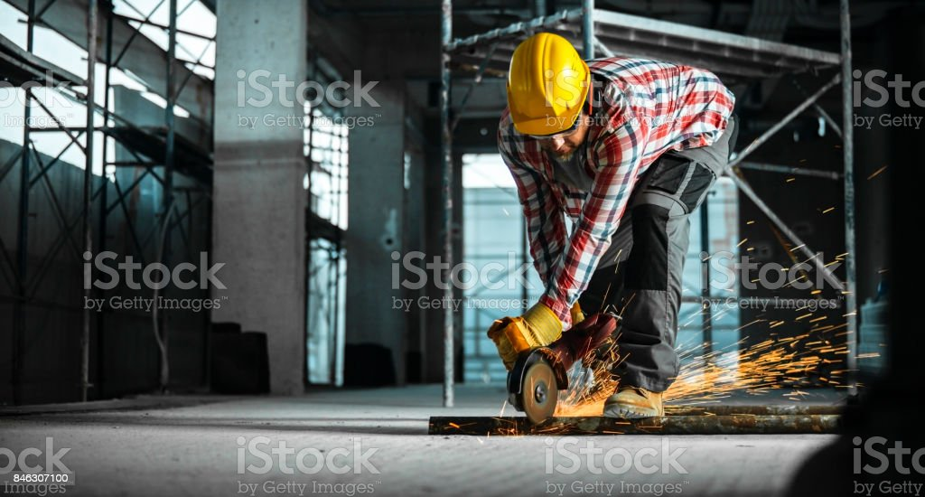 Grinder being used to cut through metal pipe on floor stock photo