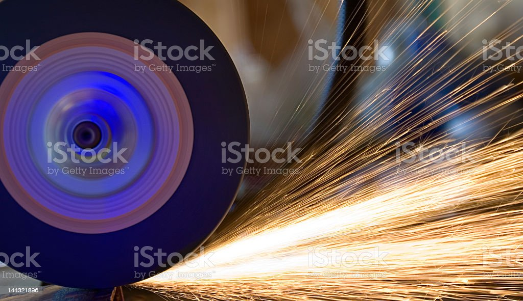 A grinder grinding a piece of metal and shooting sparks royalty-free stock photo
