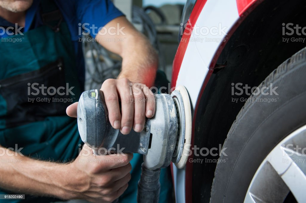 Grinder in the hands of a man who sharpen a car varnish in the car shop. stock photo