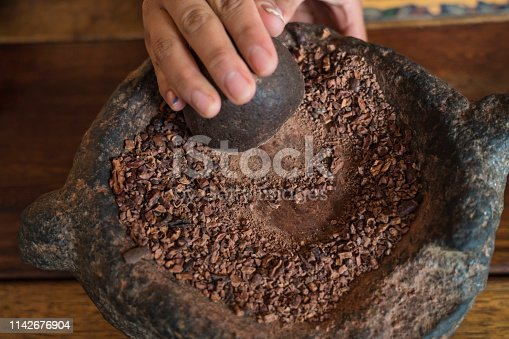 Hand grinding cocoa beans with round stone