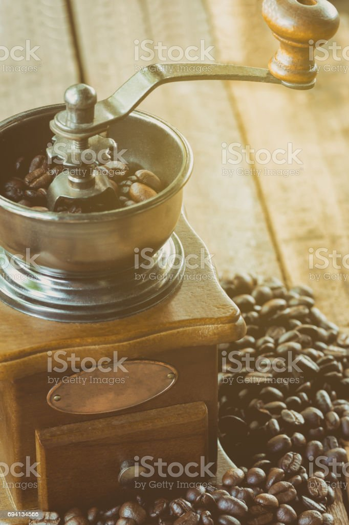 Grinding coffee beans by rotary coffee grinder under moning light...