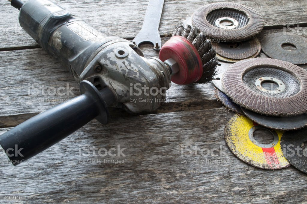 Grinding machine and discs on an old wooden table. stock photo