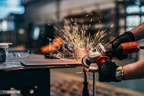 Grinding metal with small grinder, close-up.