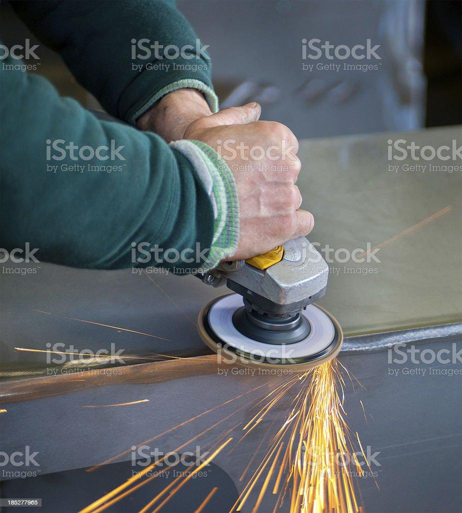 a worker smooths a weld