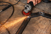 hand holding grinder and grinding steel have spark spread around