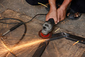 hand holding grinder and grinding steel have spark spread aroundhand holding grinder and grinding steel have spark spread around