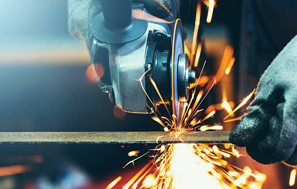 Grinding steel tube. Closeup front view of unrecognizable man cutting thin metal rod with electric grinder. Usual day in a workshop. Sparks flying all over. grinding stock pictures, royalty-free photos & images