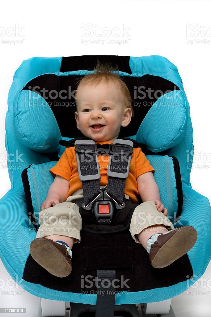 Grinning baby boy sitting in blue and black covered car seat royalty-free stock photo