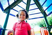 Carefree elementary aged Hispanic schoolgirl spending her recess break outdoors on playground equipment.