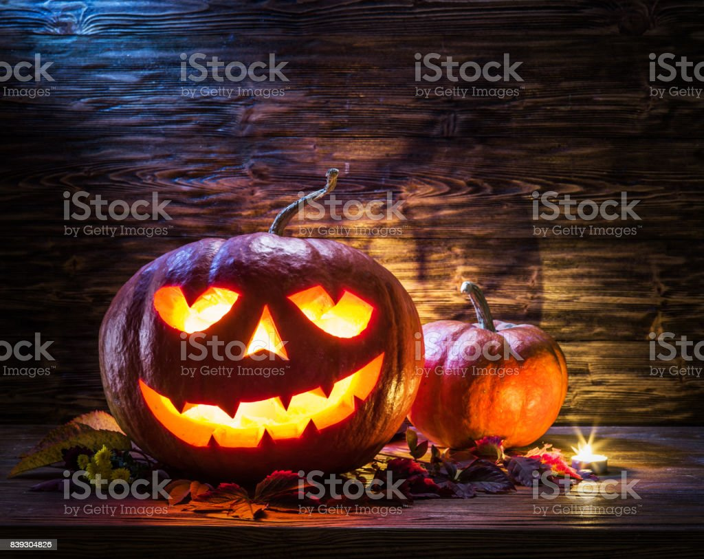 Grinning pumpkin lantern or jack-o'-lantern is one of the symbols of Halloween. Halloween attribute. Wooden background. stock photo