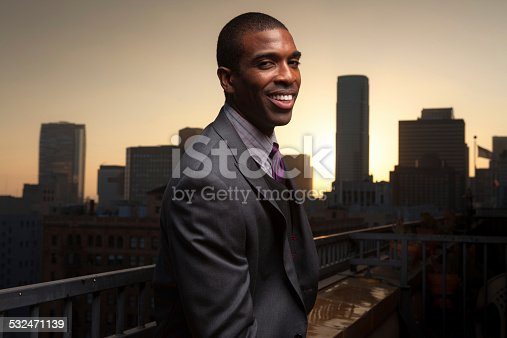 A young man wearing a three piece suit stands on a balcony overlooking the financial district of Downtown Los Angeles, looking back at the camera with a confident grin.