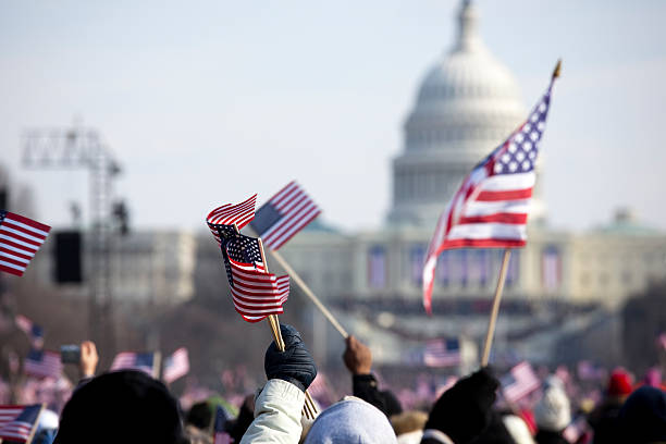 a grip of people holding flags in front of the white house - inauguration stok fotoğraflar ve resimler