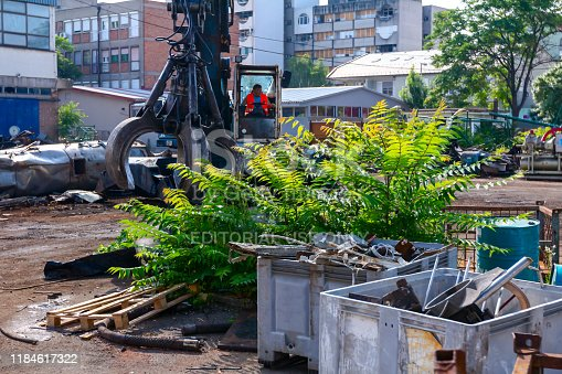 Zrenjanin, Vojvodina, Serbia – June 08, 2018: View on machine, loader manipulator with hydraulic grappling claw until is collecting, moving old steel, scrap metal.