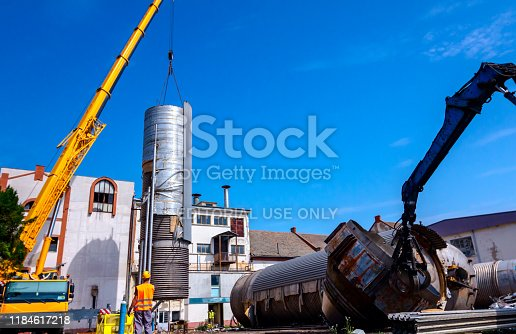 Zrenjanin, Vojvodina, Serbia – June 08, 2018: Loader machine with hydraulic grappling claw and crane are bringing down heavy metal silo in industrial complex.