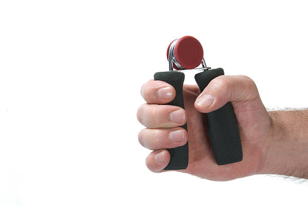 a gripping exercise working out muscles in your hand - hand grip stock photos and pictures