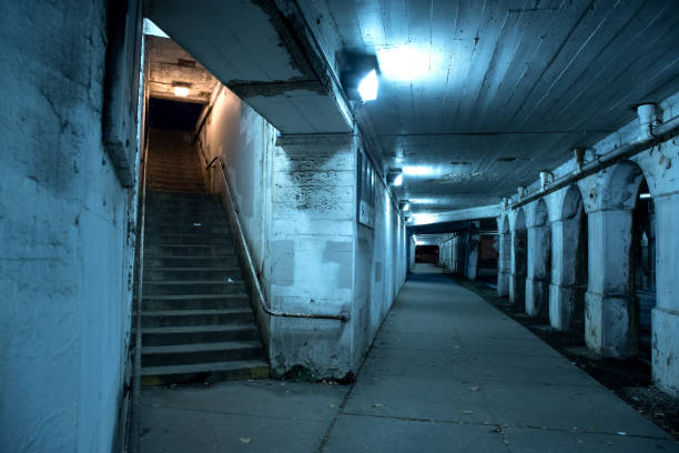 Gritty dark Chicago city street under industrial bridge viaduct tunnel with a stairway to Metra train station at night. stock photo