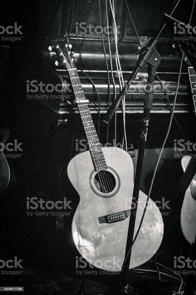 Gritty image of an acoustic guitar resting against a piano stock photo