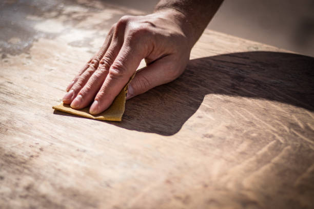 Gritty weathered man's hand sanding a wooden surface stock photo