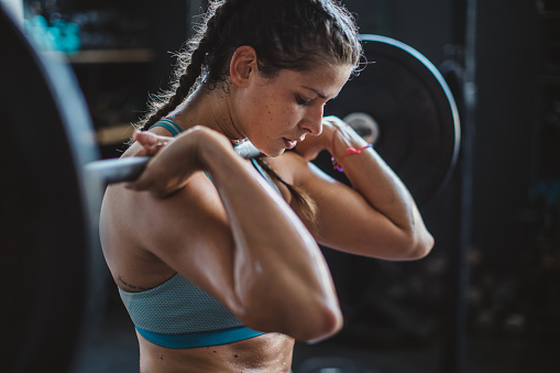 Woman weightlifting with barbell at gym
