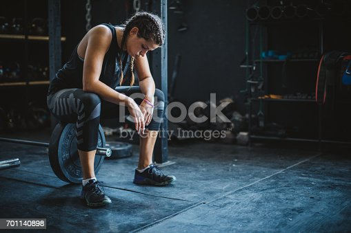 Woman resting after weightlifting in a cross training gymnasium