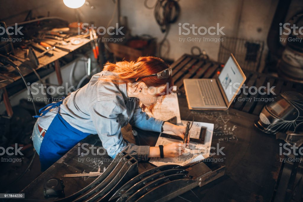 Young mechanic woman working at her workshop