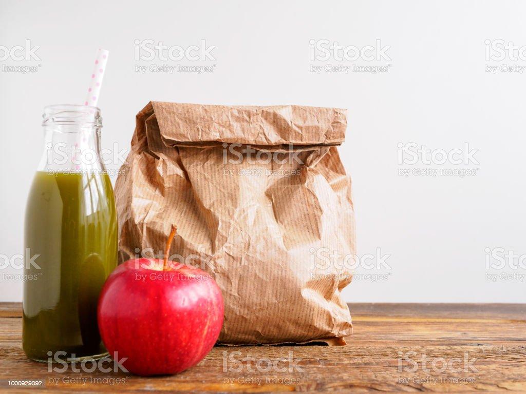 Grüner Smoothie, roter Apfel und eine Papiertüte stock photo