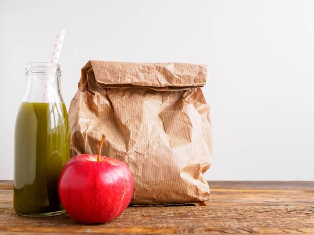 grüner smoothie, roter apfel und eine papiertüte - lunchrast bildbanksfoton och bilder