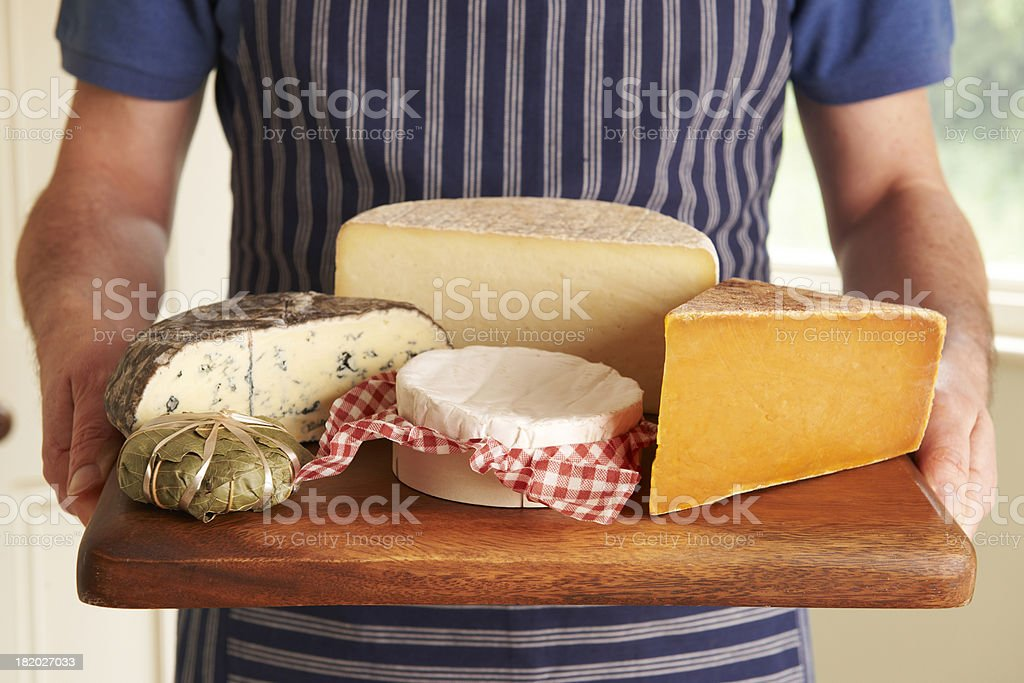 Grocer Holding Board With Selection Of Luxury Cheeses stock photo
